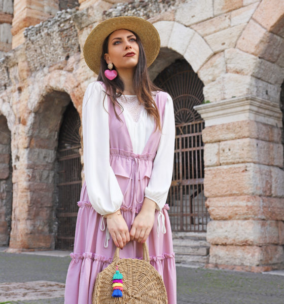 Abito rosa vintage-style a balze e una borsa di paglia in giro per Verona